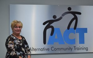 Barb Wright stands by our logo posted on the wall